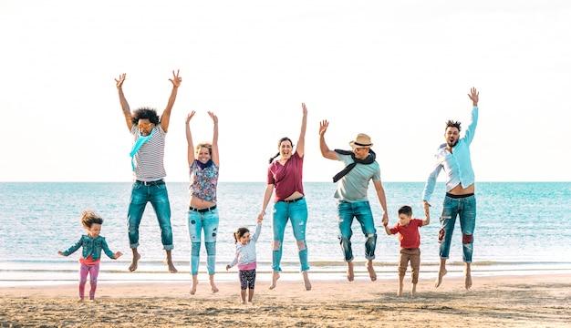 Famiglie multirazziali felici che saltano insieme al tenersi per mano della spiaggia