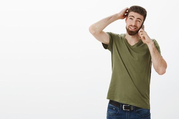 Fammi pensare. uomo carino con la barba che fa piani come parlare con un amico tramite smartphone essendo insicuro pensando come data di raccolta per incontrare grattarsi la testa incerta strabismo e guardando oltre il muro bianco