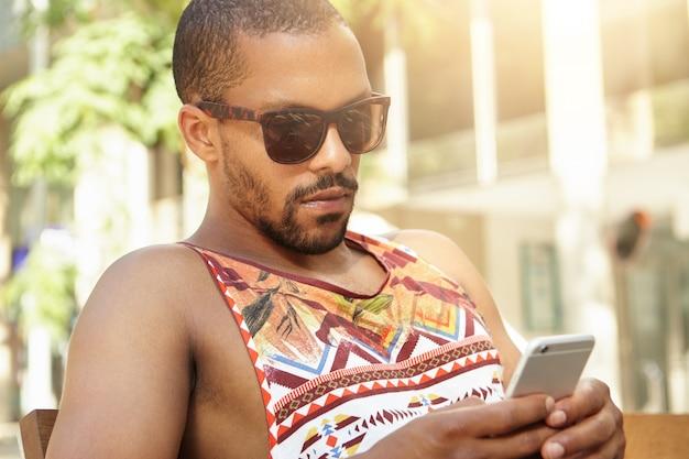 Famoso blogger africano alla moda in ombra che si nasconde dalla calura estiva nel parco usando lo smartphone per condividere il suo nuovo post tramite i social network, con un aspetto serio e concentrato. uomo di colore che manda un sms all'aperto