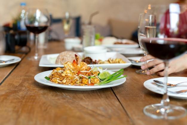 Famoso pad thai noodles con gamberi e bicchiere di vino rosso sul tavolo di legno.