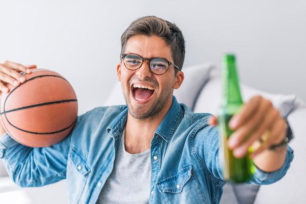 Fan del basket giovane allegro che guarda tv e che tiene palla di pallacanestro mentre gesturing