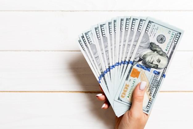 Fan di banconote da cento dollari in mano femminile