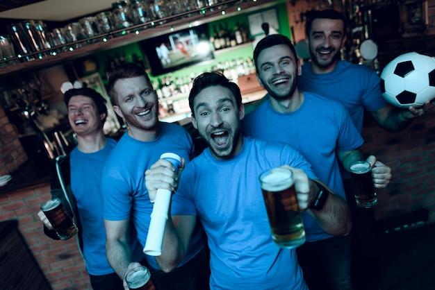 Fan di calcio che celebrano obiettivo e che bevono birra.