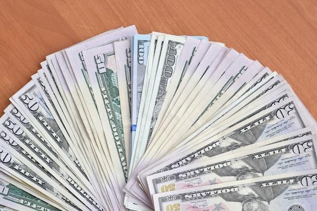 Fan di molte cento e cinquanta banconote in dollari sulla fine di legno della superficie del fondo su