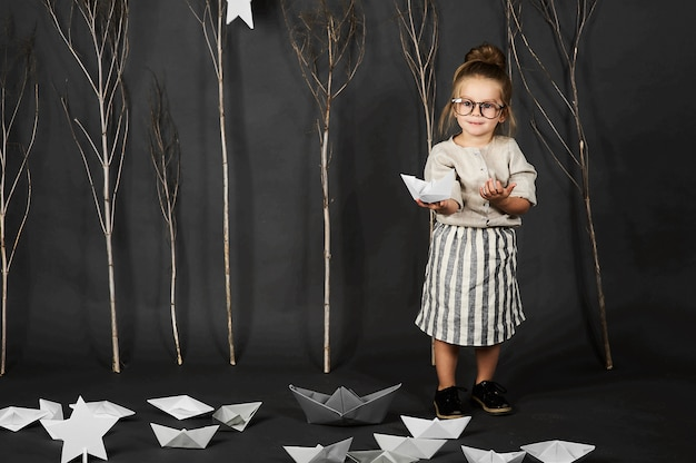 Fanny bambina con gli occhiali su sfondo grigio con stelle, alberi e barche di carta