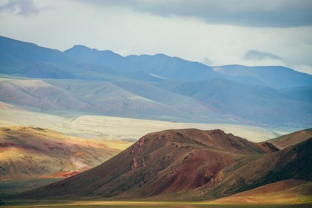 Fantasia vasto paesaggio con vivaci montagne multicolori alla luce del sole.