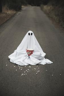 Fantasma con scatola di popcorn seduto su strada con diffusione di grani