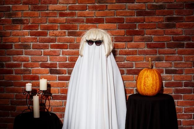 Fantasma in occhiali da sole e parrucca in posa sul muro di mattoni