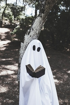 Fantasma in piedi all'albero e libro di lettura