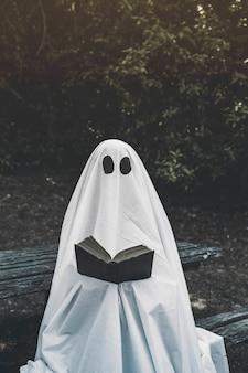 Fantasma seduto sulla panchina e leggendo il libro