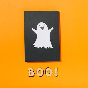 Fantasma sorridente su un pezzo di carta nera con boo! iscrizione qui sotto