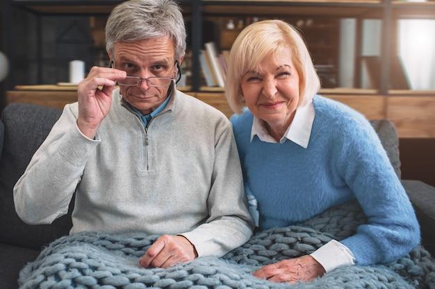 Fantastica coppia seduta sul divano con una coperta
