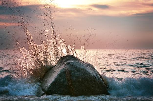Fantastica onda con schizzi al tramonto