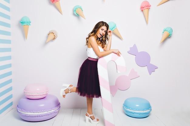 Fantastica ragazza che indossa una gonna lussureggiante viola scuro che tiene un bastoncino di zucchero rosa e in piedi su una gamba con un sorriso. ritratto integrale della ragazza allegra divertendosi sulla festa dolce a tema.