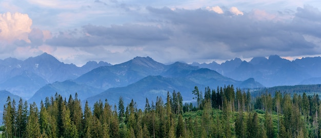 Fantastiche montagne innevate nelle splendide nubi cumuliformi