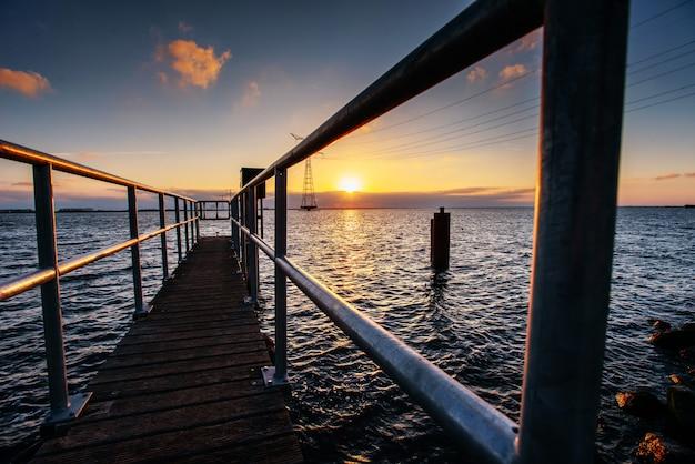 Fantastico tramonto che illumina il lungo molo sul lago
