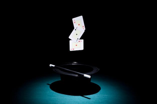 Far luce sul cappello con una carta da gioco di tre assi
