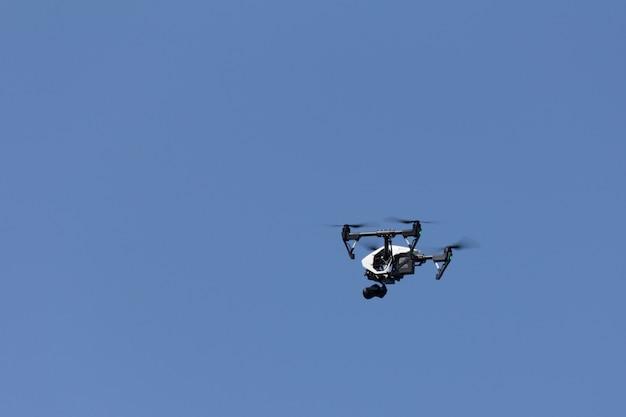 Far volare un quadricoptero sta filmando contro il cielo blu chiaro