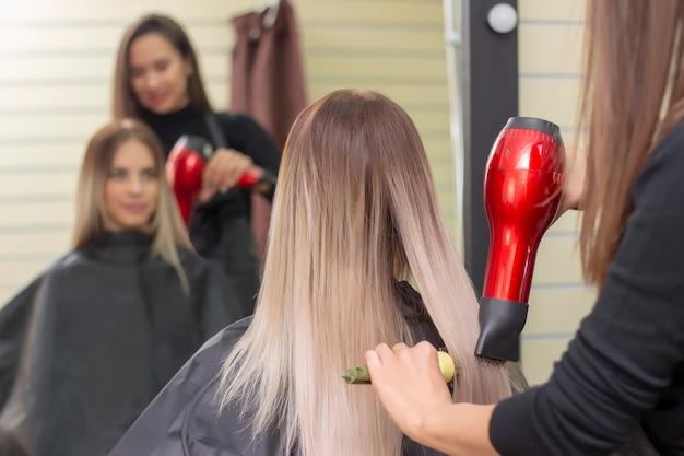 Fare acconciatura usando l'asciugacapelli. donna con i capelli lunghi biondi in un salone di bellezza. barbiere.