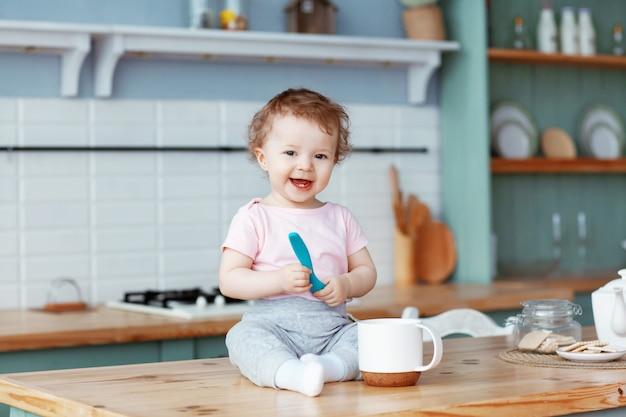 Fare da baby-sitter felice nella cucina sul tavolo che tiene un cucchiaio di plastica per alimento in sue mani e che sorride ampiamente