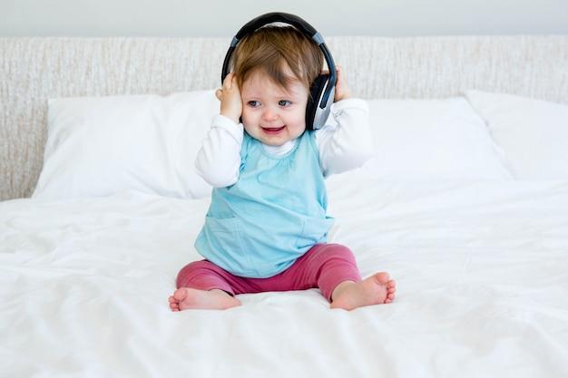 Fare da baby-sitter sorridente su un letto che gioca con le cuffie