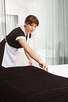 Fare il letto è come l'arte. tiro al coperto di cameriera in uniforme, mettere la coperta sul letto mentre si pulisce l'appartamento dell'hotel o la casa dei proprietari, cercando di pulire la polvere da tutta la superficie e offrire il miglior servizio