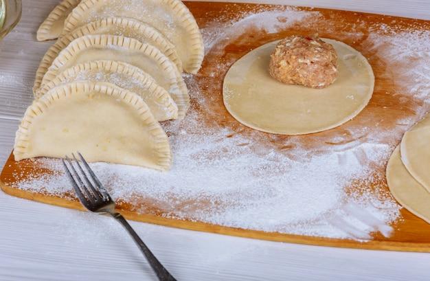 Fare pasticci fatti in casa con carne su tavola di legno