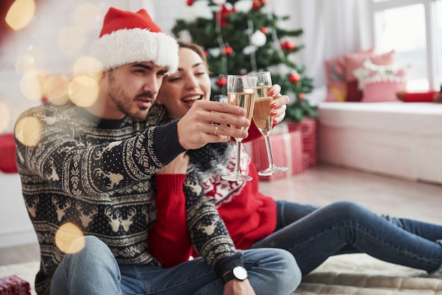 Fare un brindisi. due persone siedono sul pavimento e festeggiano il nuovo anno