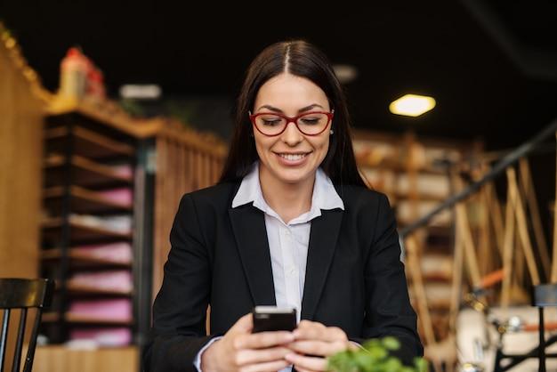 Fare una pausa. giovane donna moderna di affari che prende una pausa dal lavoro in una caffetteria. usando il telefono con il sorriso sul viso.