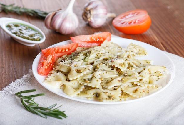 Farfalle al pesto, pomodori e formaggio su una tovaglia di lino