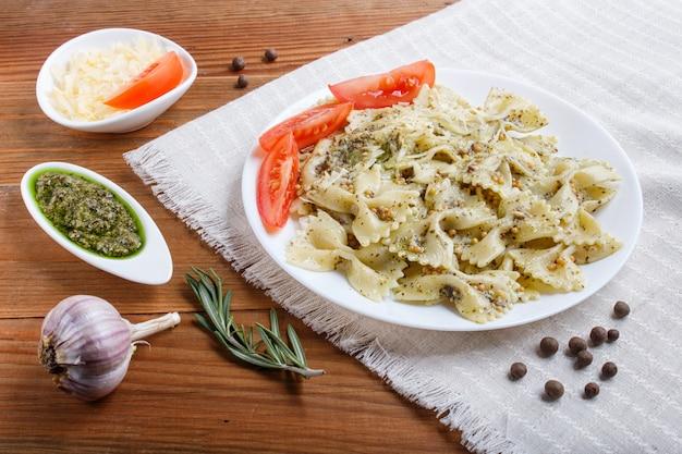 Farfalle con pesto, pomodori e formaggio su una tovaglia di lino