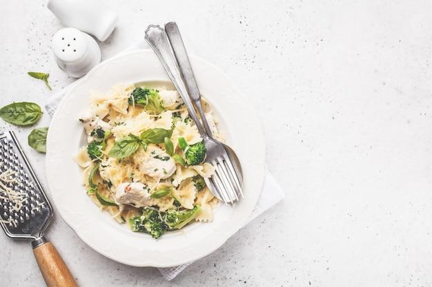 Farfalle di pasta italiana con broccoli, pollo e formaggio in un piatto bianco.