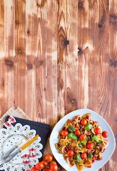 Farfalle di pasta italiana in salsa di pomodoro e vari tipi di verdure