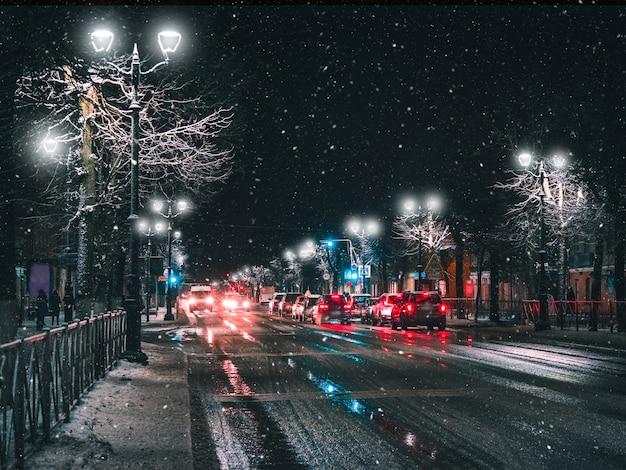 Fari nel traffico cittadino di notte invernale.
