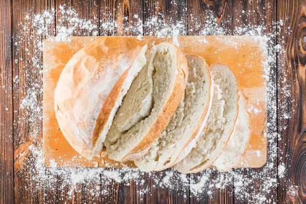 Farina bordo oltre il bordo del tagliere con fette di pane