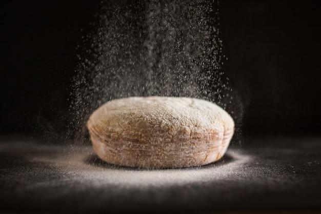 Farina che viene spruzzata sul pane appena sfornato