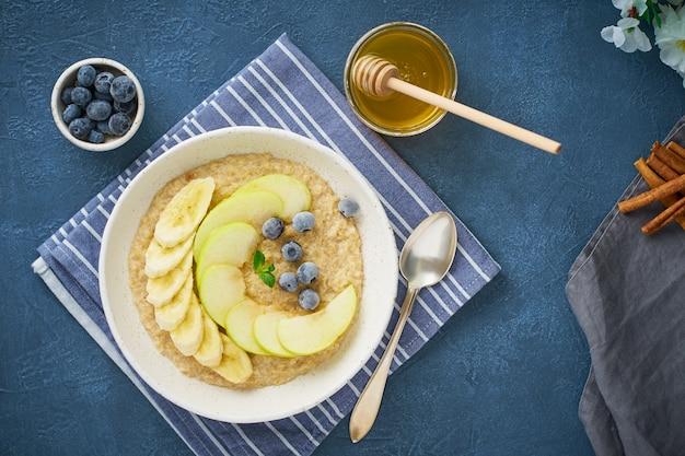 Farina d'avena con banane, mirtilli, marmellata, miele, tovagliolo blu su sfondo blu pietra