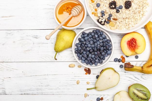 Farina d'avena con frutta e miele su una tavola di legno bianca
