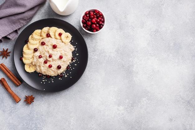Farina d'avena con latte con mirtilli rossi alla banana e semi di sesamo. una tazza di caffè, concetto sano della prima colazione. copia spazio