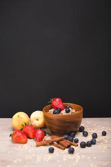 Farina d'avena con mirtilli e fragole in un piatto di legno. pesche e frutti di bosco sul tavolo.