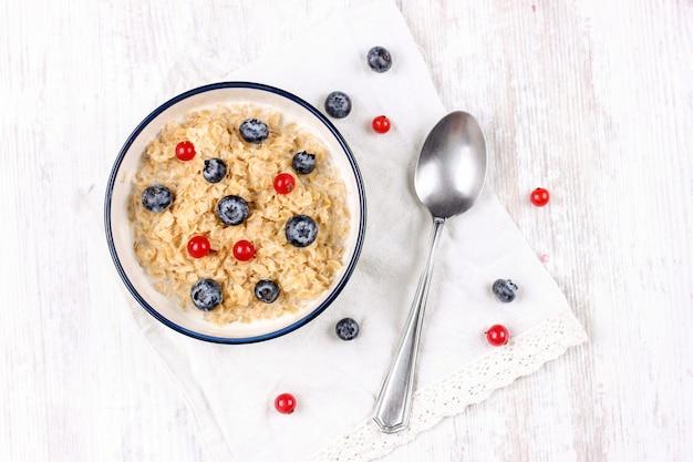 Farina d'avena con mirtilli freschi e bacche di ribes rosso. dieta alimentare - porridge di farina d'avena in un piatto con un cucchiaio.