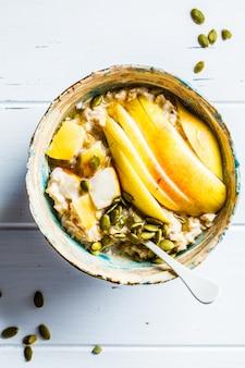 Farina d'avena con semi di pera e zucca in ciotola di ceramica su superficie di legno bianco, vista dall'alto,