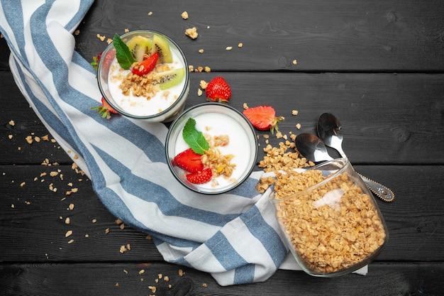 Farina d'avena con yogurt e frutti di bosco su un fondo di legno nero