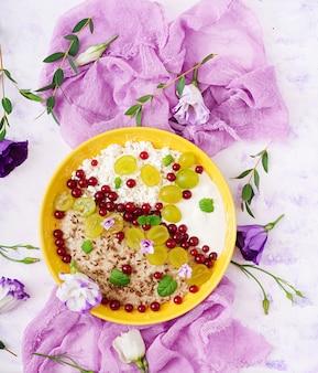 Farina d'avena deliziosa e sana con uva, yogurt e ricotta. colazione salutare. cibo fitness. nutrizione appropriata. disteso. vista dall'alto.