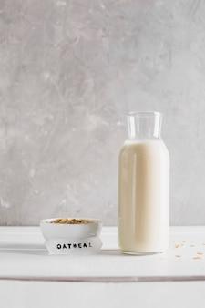 Farina d'avena di vista frontale con la bottiglia per il latte sulla tavola