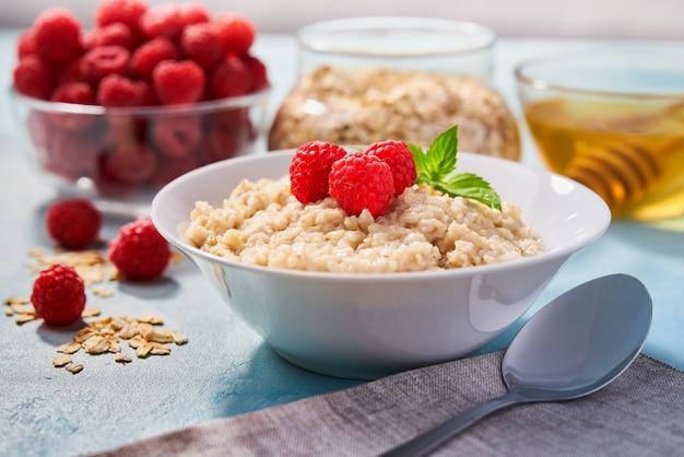 Farina d'avena fatta in casa con lamponi freschi e miele biologico per colazione su turchese.