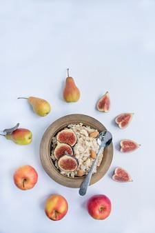 Farina d'avena in una ciotola con fichi freschi, mandorle e anacardi farina d'avena con frutta. bianca .