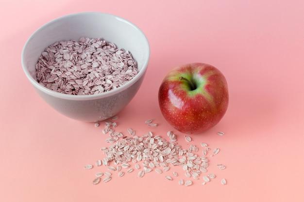 Farina d'avena in una ciotola e mela rossa lucida
