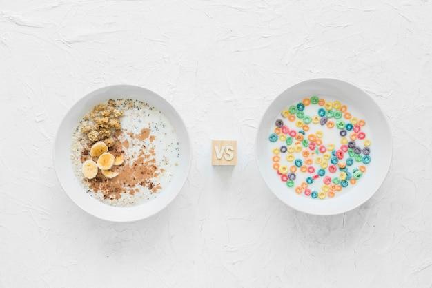 Farina d'avena inzuppata contro i cereali sulla ciotola bianca sopra il contesto strutturato