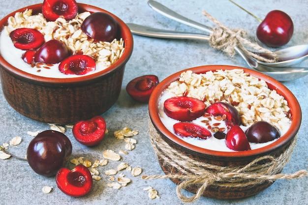 Farina d'avena per la colazione con yogurt e ciliegie. kefir e farina d'avena. probiotici. latticini fermentati.